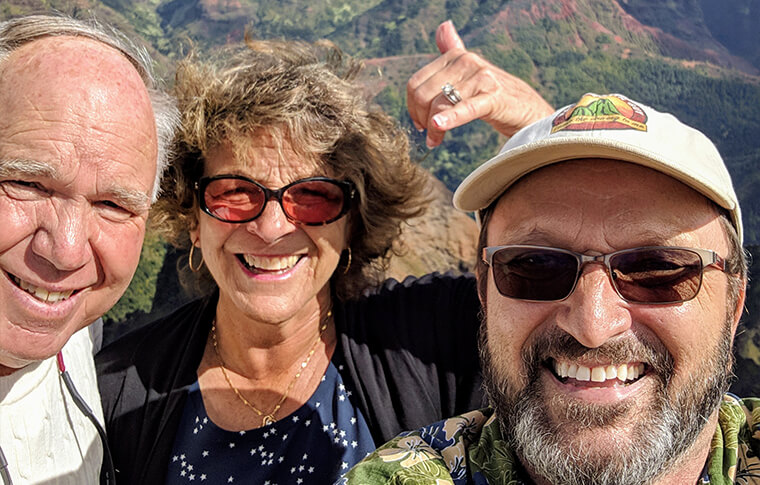 Smiling couple taking picture with tour guide with canyon background