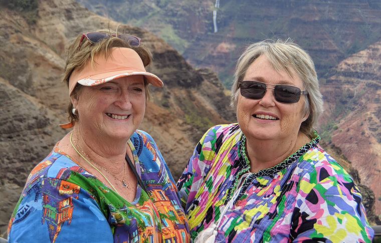 2 smiling ladies taking a picture with the awesome canyon in the background