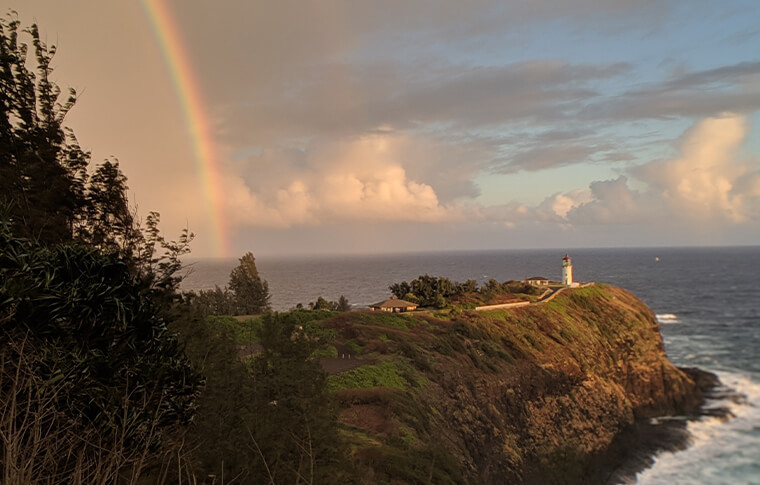 Sunset and rainbow with a lighthouse perched at the end of the cliff