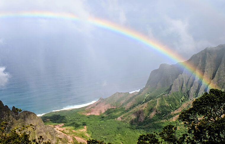Beautiful rainbow stretching across an enormous gorge with the ocean in the background