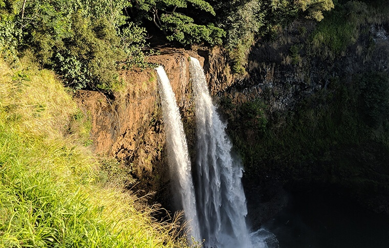 Cascading waterfall over sun soaked cliffs