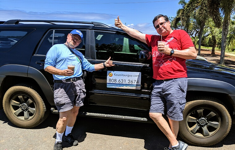 Tour clients in front of the Kauai Tour Guy's car with their thumbs up